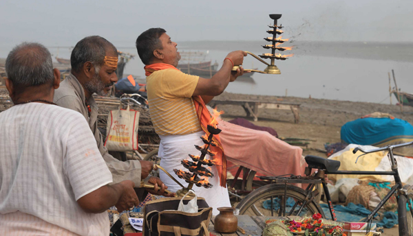 PRAYAGRAJ, OCT 31 (UNI):- A priest offering Ganga aarti after taking a dip in Holy Ganga the Sangam, during smoggy morning in Prayagraj on Thursday.UNI PHOTO-24U