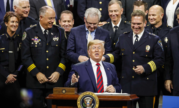 CHICAGO, Oct. 29 (Xinhua) -- U.S. President Donald Trump (C) signs an executive order after addressing the International Association of Chiefs of Police Conference at the McCormick Place Convention Center in Chicago, the United States, on Oct. 28, 2019. Xinhua/UNI PHOTO-5F