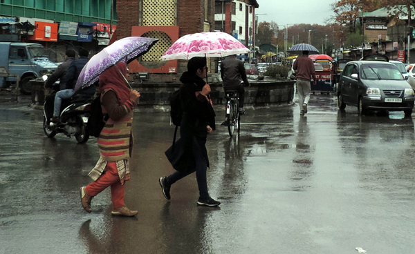 SRINAGAR, NOV 6 (UNI) Women with Umbrellas walking down the capital city Lal Chowk amid rainfall and spontaneous general strike on the 94th consecutive day on Wednesday. UNI SRN PHOTO 3