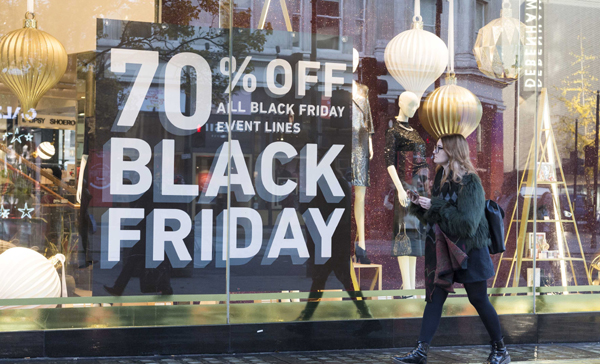 "LONDON, Nov. 29 (Xinhua) -- A woman walks past a shop window advertising ""Black Friday"" sales in London, Britain on Nov. 29, 2019. Xinhua/UNI PHOTO-16F"