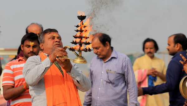 PRAYAGRAJ, NOV 25 (UNI)- Devotees offering Ganga aarti after taking holy dip on foggy Monday morning in Prayagraj. UNI PHOTO-6u