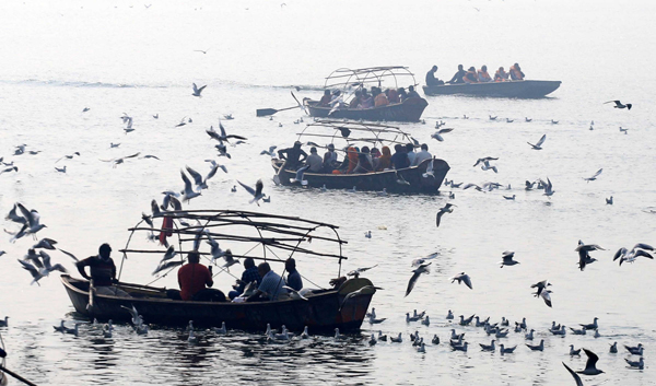 PRAYAGRAJ, NOV 23 (UNI):- People feeding migratory birds in Yamuna river in Prayagraj on Saturday.UNI PHOTO-8U