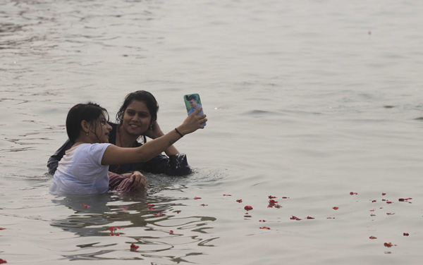 Girls taking selfie while taking a dip at Sangam, during a smoggy morning