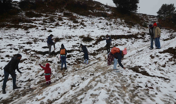 SHIMLA, NOV 28 (UNI):-Tourists enjoying season first snowfall at Kuffri, in Shimla on Thursday.UNI PHOTO-55U