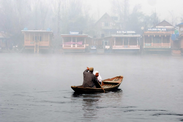 SRINAGAR, DEC 5 (UNI) A boatman rowing his Shikara taking across the famous Dal Lake an elderly woman amid dense fog as temperature dipped to minus 3.5 in Srinagar on Thursday. UNI SRN PHOTO 8