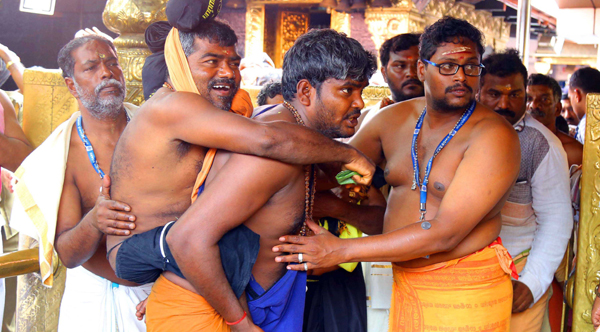 SABARIMALA ,DEC 1 (UNI)-A devotee carries his friend disabled devotee offering their prayers, during the Mandala Makaravilakku season in Sabarimala on Sunday.UNI PHOTO-16U
