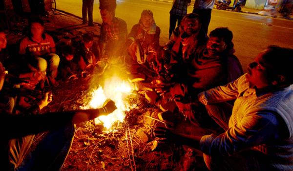 Kolkata: People warm themselves around the fire on a chilly winter evening in Kolkata on Dec 22, 2019. (Photo: Kuntal Chakrabarty/IANS)