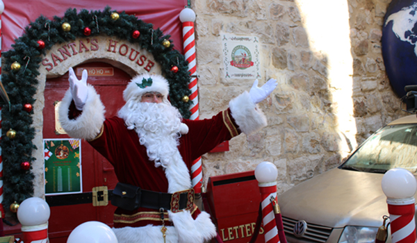 """(191219) -- JERUSALEM, Dec. 19, 2019 (Xinhua) -- The """"Jerusalem Santa"""", a Palestinian dressed up as Santa Claus, gestures outside his Santa's House in the Jerusalem's Old City on Dec. 19, 2019, as people around the world prepare to celebrate the festival. (Xinhua/Shang Hao)"""