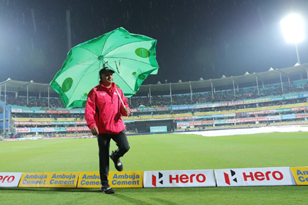 Guwahati: Umpire Virender Sharma holds an umbrella as he inspects the outfield after rains delays the start of 1st T20I match between India and Sri Lanka at Barsapara Cricket Stadium in Guwahati on Jan 5, 2020. (Photo: IANS)