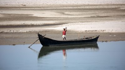 SUNSARI, Jan. 3, 2020 (Xinhua) -- A man prepares to ride a boat to cross Sapta Koshi river at Koshi Tappu Wildlife Reserve in Sunsari, Nepal, Jan. 2, 2020. Koshi Tappu Wildlife Reserve is popular for bird watching and observing the conservation of last remaining population of wild water buffalo, locally known as Arna. (Photo by Sunil Sharma/Xinhua/IANS)