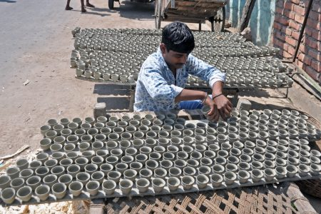 A potter busy drying freshly carved clay cups in Kolkata