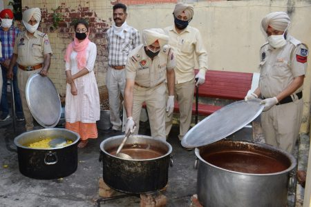 Police personnel prepare food to be distributed among the poor & homeless people