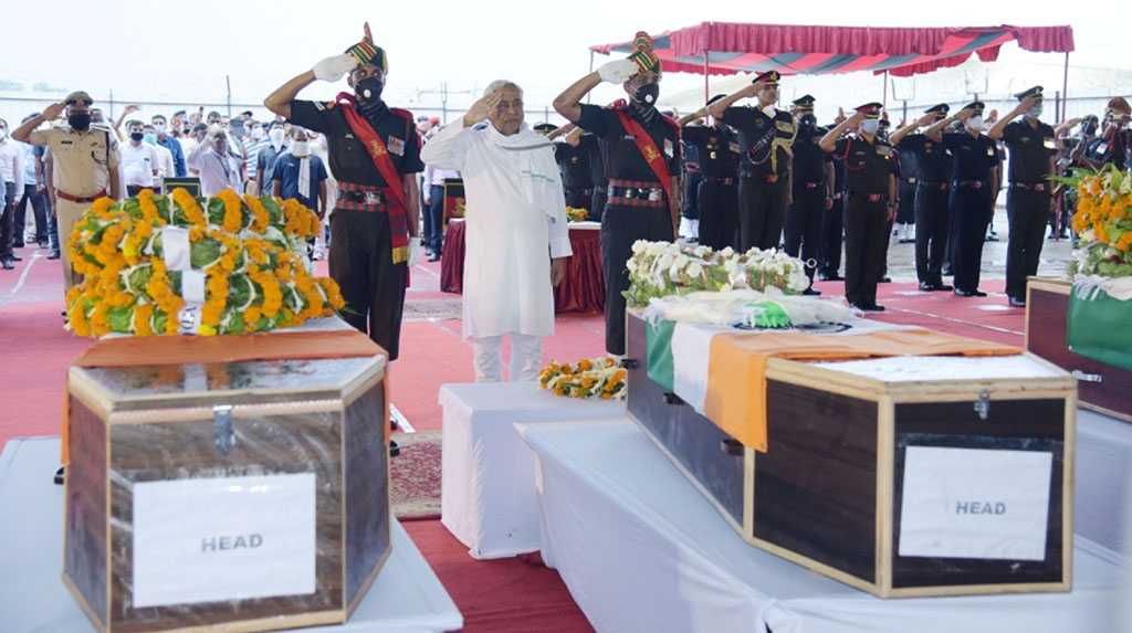 Patna: Bihar Chief Minister Nitish Kumar pays his respect to the mortal remains of martyrs who among 20 Indian soldiers killed in a clash with Chinese forces in Galwan Valley along the Line of Actual Control (LAC) in eastern Ladakh region on Monday; during wreath laying ceremony at Jay Prakash Narayan International Airport in Patna on June 18, 2020. (Photo: IANS)