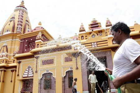 A temple staff washes the Birla temple as it gears up to re-open