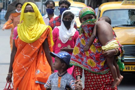 Migrant returnees walk past a Kolkata street after arriving in the city