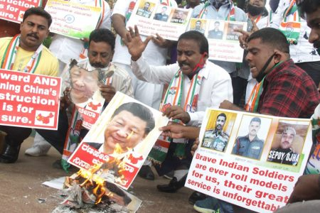 Youth Congress activists burn the posters of Chinese President Xi Jinping