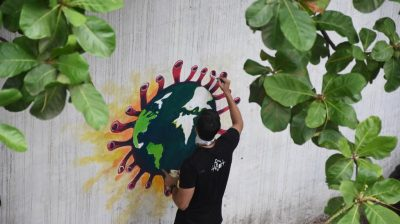 Mumbai: An artist paints a wall graffiti of the 'Earth trapped in COVID-19 pandemic' in Mumbai on June 2, 2020. (Photo: IANS)