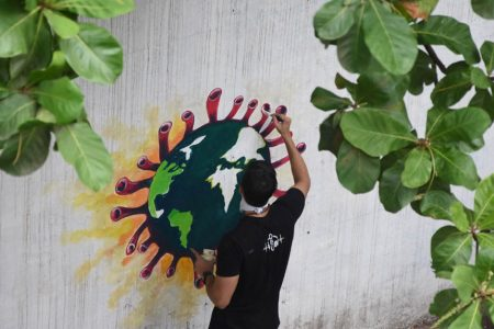 An artist paints a wall graffiti of the 'Earth trapped in COVID-19 pandemic'