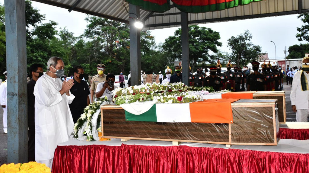 Bhubaneswar: Odisha Chief Minister Naveen Patnaik pays tributes to Chandrakant Pradhan and Naib Subedar Nanduram Soren, two Indian Army jawans from Odisha, who were killed during a clash with Chinese soldiers in Ladakh; at the Biju Patnaik International Airport in Bhubaneswar on June 18, 2020. (Photo: IANS)