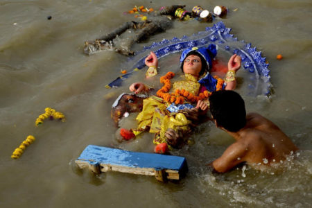 An idol of Lord Vishwakarma being immersed in the Ganga river